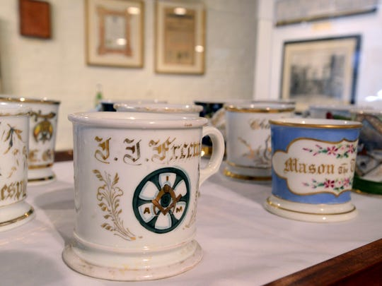 Shaving mugs, most marked with fraternal organization writings and logos, are displayed at the Georgian Museum in downtown Lancaster.