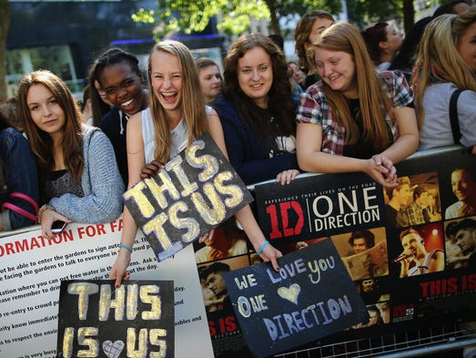 One Direction fans take their positions in London's Leicester Square ahead of the premiere of the band's new film 'This Is Us' on Tuesday evening at the Empire Cinema.