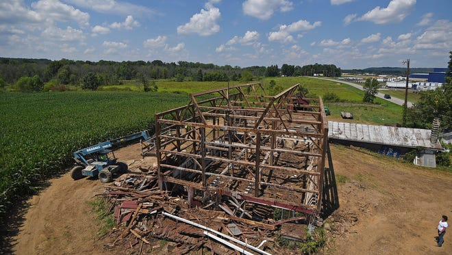 Lisa Smith of Ohio Valley Reclaimed Wood watches as the Kisling Barn outside Lexington is carefully disassembled.
