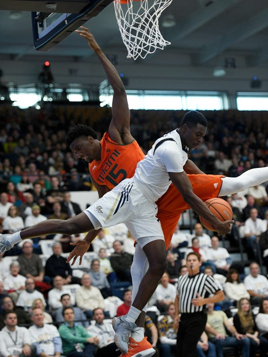 Miami center Ebuka Izundu (15) battles for the ball against George Washington guard Terry Nolan Jr. (1) during the first half of an NCAA college basketball game, Saturday, Dec. 16, 2017, in Washington. (AP Photo/Nick Wass)