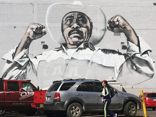 "A large mural titled ""Animo Sin Fronteras"" by muralist El Mac on the rear wall of a building facing a parking lot along the 300 block of E. Mills Ave. at N. Stanton St. in downtown El Paso"