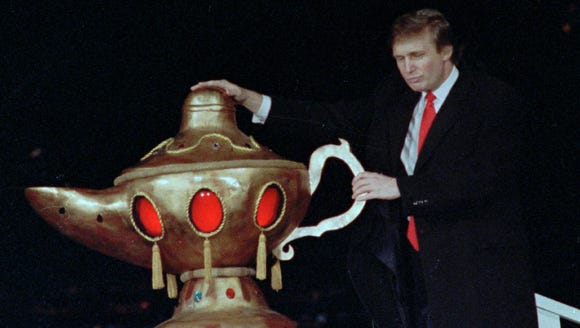 Donald Trump rubs a genie's lamp during the grand opening