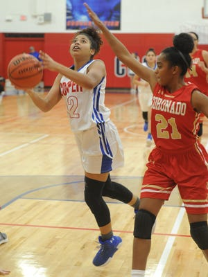 Cooper's T'Kiya Smith (12) drives to the basket as Lubbock Coronado's Malia Montes (21) defends. Cooper beat the Lady Mustangs 67-50 in the District 4-5A game Friday, Jan. 19, 2018 at Cougar Gym.