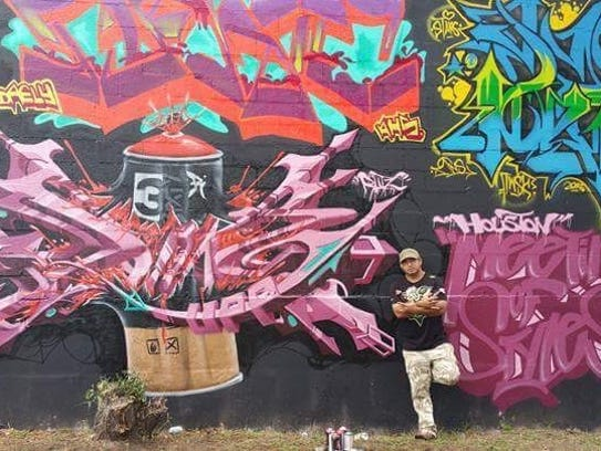 Inx Garcia poses infront of a mural her painted in