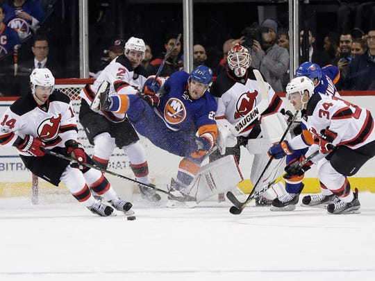 Islanders' Anders Lee, center, Devils goalie Keith Kinkaid (1), John Moore (2) and Steven Santini (34) watch as Devils' Adam Henrique (14) gains control of the puck during the first period of a game Friday, March 31, 2017, in New York.