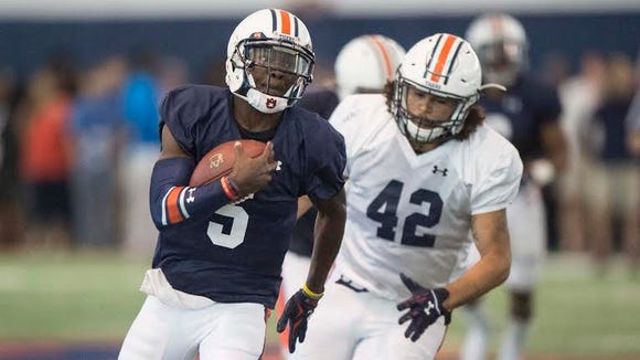 Auburn quarterback John Franklin III (5) running away from linebacker Tre' Threat (42) during a spring ball scrimmage session.