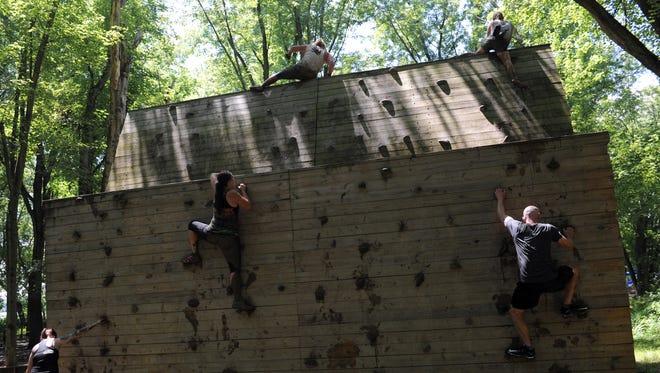Challengers work their way up a climbing wall during a previous Indian Mud Run at Lake Park in Coshocton. Organizers are expecting more than 500 people to compete and many more to watch and cheer on the competitors.