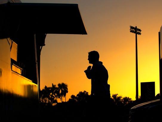 Bishop Verot coach Matt Herting is silhouetted by the