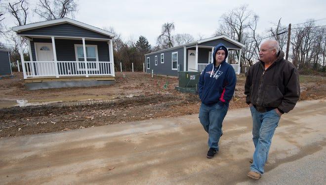 Breanna Waltz and George Makdad walk next to new manufactured homes at St. Jones Landing in Magnolia.