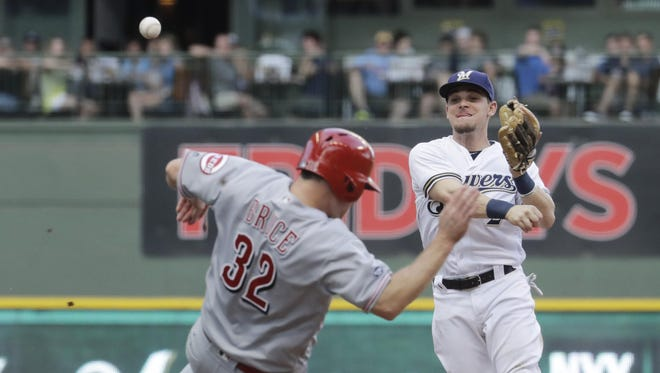 Cincinnati Reds' Jay Bruce is safe at second as Milwaukee Brewers' Scooter Gennett tries to turn a double play on a bases loaded ball hit by Adam Duvall during the ninth inning of a baseball game Saturday, May 28, 2016, in Milwaukee. Duvall was out at first as the Reds scored a run.