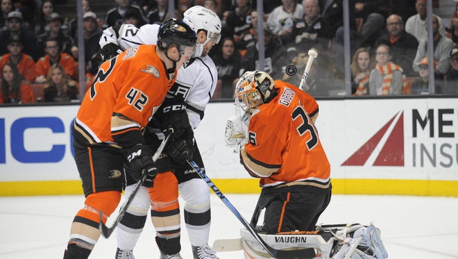 Anaheim Ducks defenseman Josh Manson (42) helps goalie John Gibson (36) defend the goal against Los Angeles Kings center Anze Kopitar (11) during the first period at Honda Center.