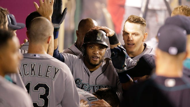 Seattle Mariners' Robinson Cano, center, celebrates his home run with teammates during the eighth inning of a baseball game against the Los Angeles Angels, Friday, June 26, 2015, in Anaheim, Calif.