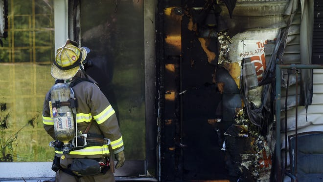 A Mountain Home firefighter surveys the damage at 1201 Hallmark Circle in Mountain Home Thursday afternoon. Fire broke out on the porch of the home, potentially due to an ashtray according to fire officials.