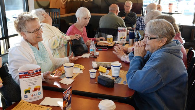 Connie Reed, left, talks with Bobby Kinsman, right, during their regular post-water-aerobics doughnut and coffee gathering at LaMar's Donuts on Nov. 7 in Fort Collins.