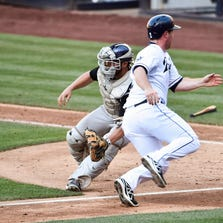SAN DIEGO, CA - AUGUST 13:  Jedd Gyorko #9 of the San Diego Padres scores ahead of the throw to Michael McKenry #8 of the Colorado Rockies during the fifth inning of a baseball game at Petco Park on August 13, 2014 in San Diego, California.  (Photo by Denis Poroy/Getty Images)