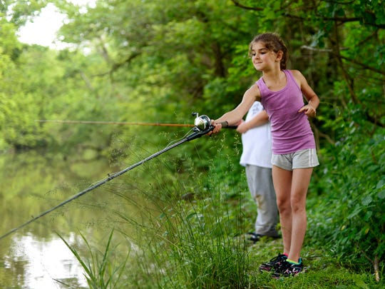 Emma-Jean Axe, 8, of Windsor Township, fishes from the creek bank. Kids ages 8 to 15 tried fishing, shooting, archery, canoeing, and other outdoor activities during Youth Field Day, a free annual event put on by the York Area Sportsman for Youth.