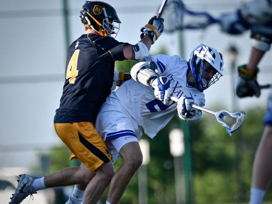 St. Xavier's Duke Alf gets a shot off despite being hit by Moeller's Jack Stahanczyk Friday, May 25th at Mason High School High School