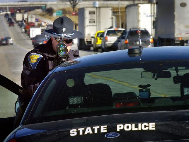 Indiana State Police trooper Tyler Utterback uses a laser radar gun to check the speed of traffic.
