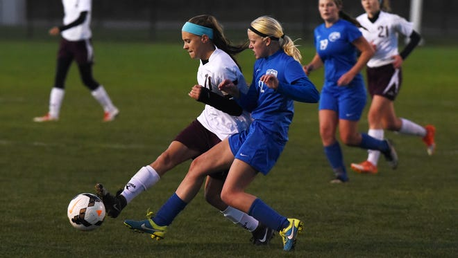 John Glenn's Harlie Gregory gets a touch on the ball in front of West Holmes' Kaylin Martin Monday night in Warsaw.