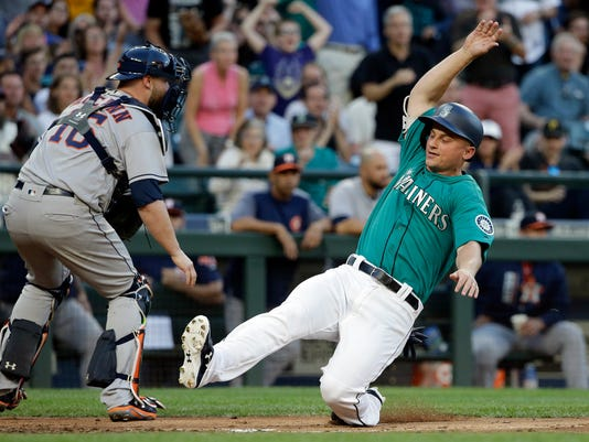 Seattle Mariners' Kyle Seager slides safely home ahead of the throw to Houston Astros catcher Brian McCann to score during the third inning of a baseball game Friday, June 23, 2017, in Seattle. (AP Photo/Elaine Thompson)
