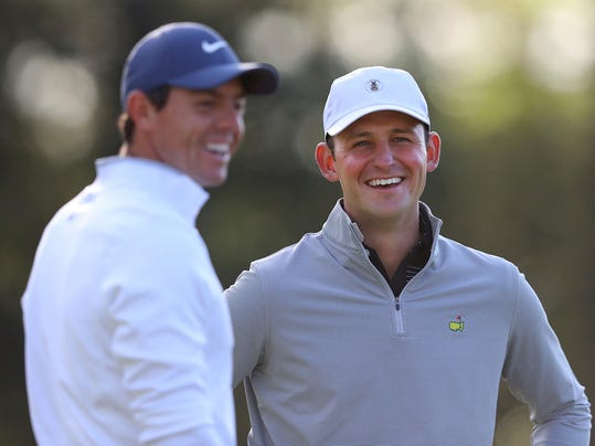 Matt Parziale, right, the U.S. Mid-Amateur champion who works as a firefighter in his hometown in Massachusetts, shares a laugh with Rory McIlroy on the first green during a practice round for the Masters golf tournament at Augusta National Golf Club in Augusta, Ga., Monday, April 2, 2018. (Curtis Compton/Atlanta Journal-Constitution via AP)