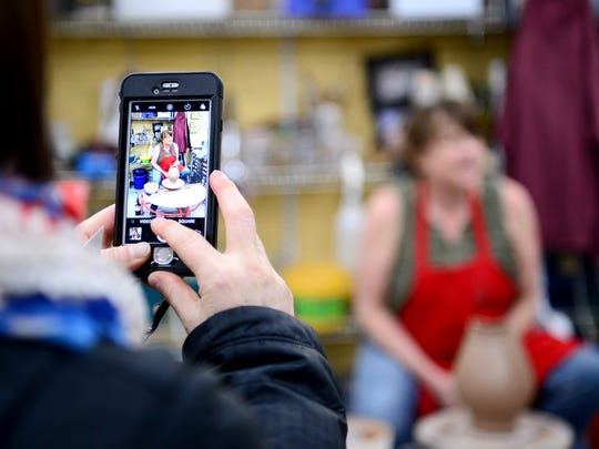 Ann Smith, with Leap Frog Tours, takes a photo of Sarah Wells Roland as she finishes up a demonstration for participants of a collaboration between Asheville Art Studio Tours and Leap Frog Tours at The Village Potters in the River Arts District.