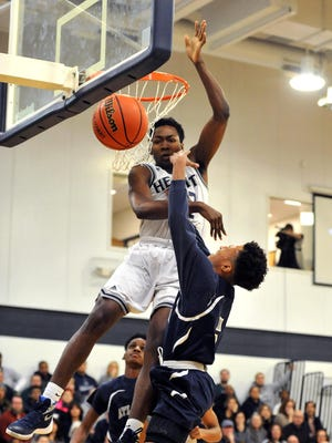 St. Augustine's Justyn Mutts (22) blocks a shot by Atlantic City's Ayshion Antino (5) during a 60-53 victory on Monday.