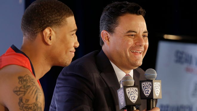 In this Oct. 23, 2014, file photo, Arizona coach Sean Miller (right) laughs as he speaks next to forward Brandon Ashley during NCAA college basketball Pac-12 media day in San Francisco. Arizona is No. 2 in The Associated Press preseason Top 25.