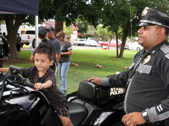 The thrill of sitting in the cockpit of a New Mexico State Police motorcycle is etched on this child's face.