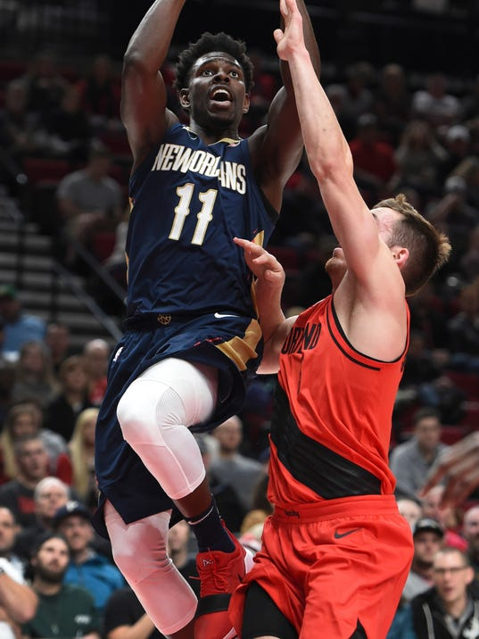 New Orleans Pelicans guard Jrue Holiday drives to the basket on Portland Trail Blazers guard Pat Connaughton during the first half of an NBA basketball game in Portland, Ore., Saturday, Dec. 2, 2017. (AP Photo/Steve Dykes)