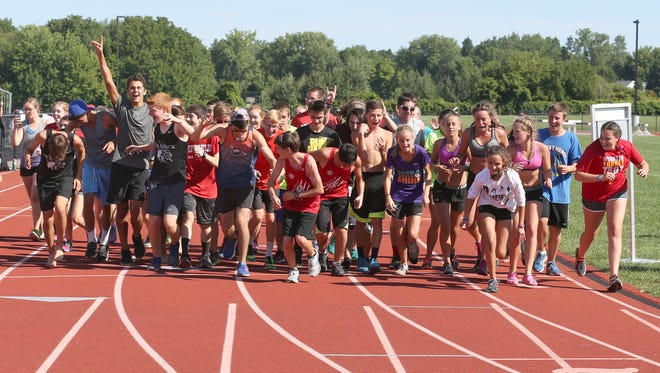 The entire Penfield cross country team run across the finish line together marking the end of their 24 hour marathon run around the track at the Penfield High School in Penfield Saturday, Aug. 27, 2016.  The run was held to raise money for the American Society for Suicide Prevention.