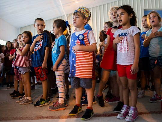 Christopher Pukin, 6, center, looks up at an American Flag and sings the national anthem during the Memorial Day Ceremony at Veterans Memorial Elementary School on Thursday, May 24, 2018.