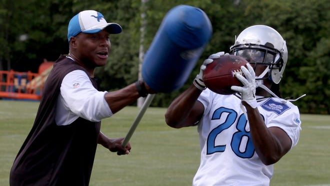 Lions defensive backs and corners coach Tony Oden applies defense to cornerback Bill Bentley during organized training activities at their practice facility in Allen Park on Wednesday.