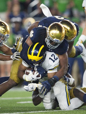 Running back Chris Evans (12) and Michigan dropped their season opener at Notre Dame.