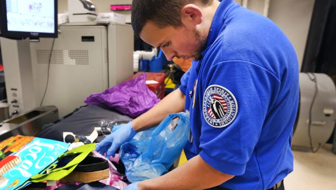 Transportation Security Officer Blake Wright does a hand search of a piece of luggage flagged and brought into the bag resolution room at Indianapolis International Airport on Monday, Oct. 19, 2015.