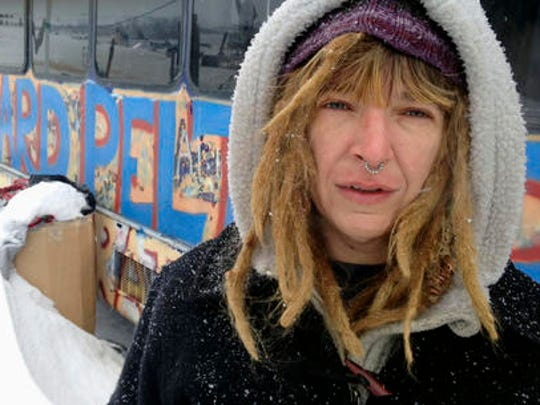 Gena Neal, from Oklahoma, poses in the bitter weather at an encampment Wednesday, Jan. 25, 2017, near Cannon Ball, N.D., to protest the Dakota Access pipeline. She is one of the protesters vowing to stay in the camp despite a Trump administration order that seeks to expedite the pipeline's completion.