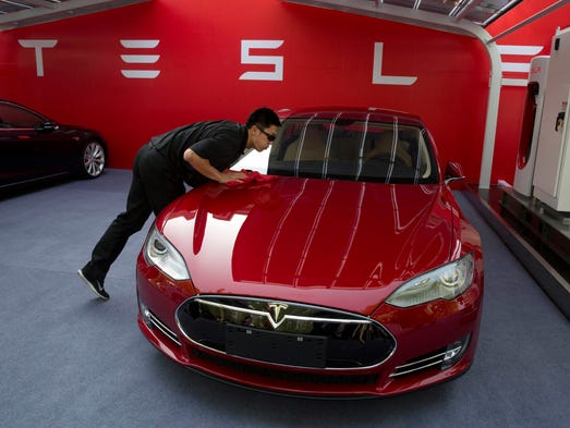 A worker cleans a Tesla Model S sedan before a event to deliver the first eight Model S cars to customers in Beijing, China, on Tuesday.