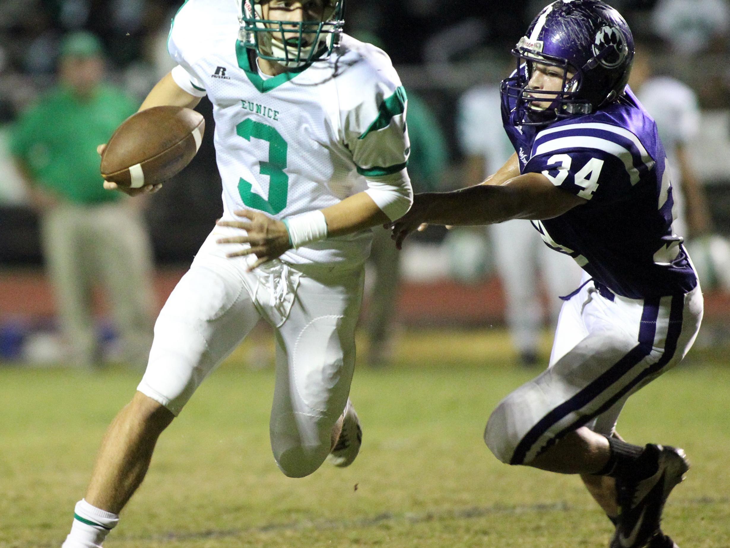 Eunice quarterback Alex Richard (3) scrambles around a Rayne defensive lineman.