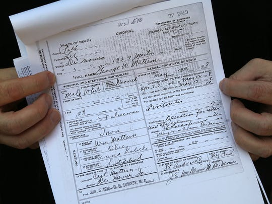 Garza holds a copy of Mattern's death certificate Wednesday. Mattern died from an infection caused by gunshot wounds suffered in a gun battle eight months before.