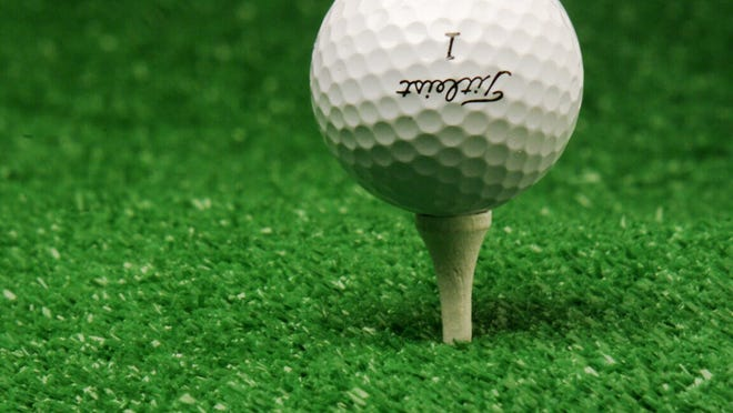 A golf ball rests on a tee.