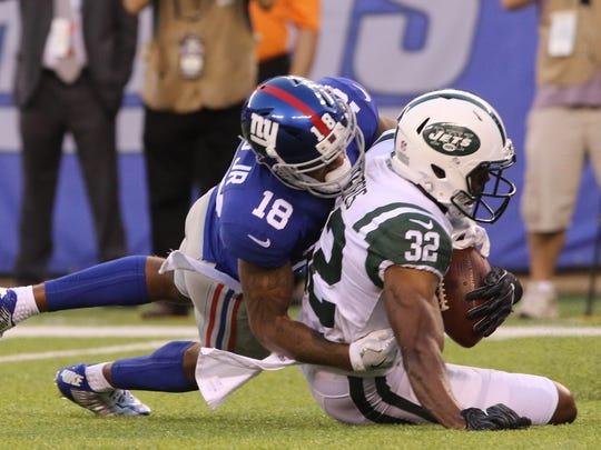 New York Giants wide receiver Roger Lewis tackles New York Jets cornerback Juston Burris after Burris intercepted an Eli manning pass in the first half.