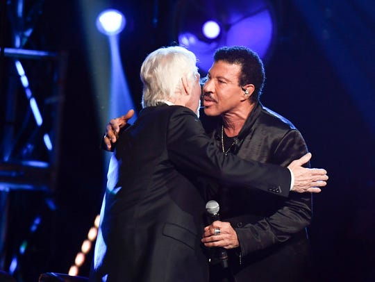 Lionel Richie hugs Kenny Rogers after performing at