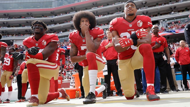 Colin Kaepernick, center, kneels in protest when he was a member of the San Francisco 49ers.