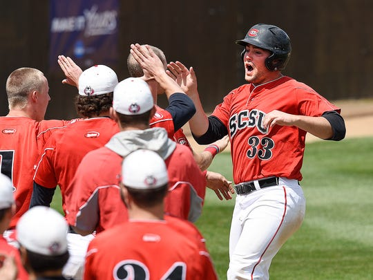 St. Cloud State's Zach Hoffmann is met by teammates after scoring against Concordia during the fourth inning of the NSIC championship game Sunday, May 15, at Joe Faber Field in St. Cloud.