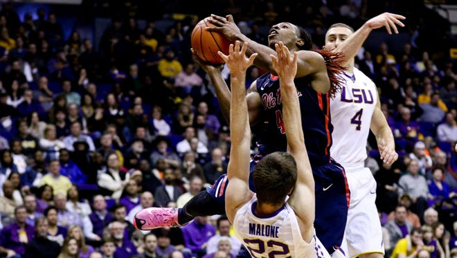 Ole Miss guard Stefan Moody (42) is called for charging against LSU Tigers center Darcy Malone (22) during the first half at the Pete Maravich Assembly Center.