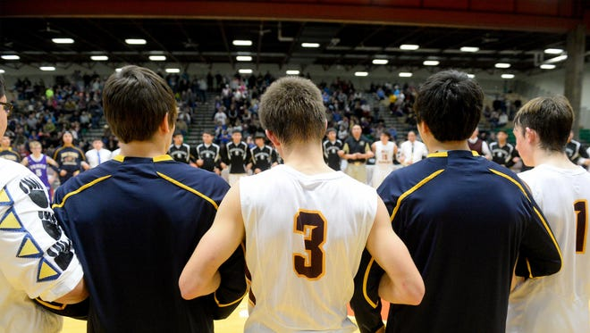 Four teams: Heart Butte, Box Elder, Belt and Power interlock arms at center court at the Northern C Divisional Basketball Tournament on Wednesday in a show of solidarity after a Montana radio personality suggested Indian schools should have their own tournament.