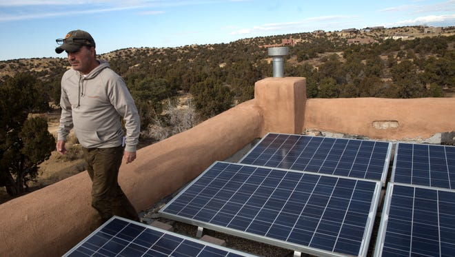 Mike Eisenfeld shows his solar panels Friday on the roof of his home in Farmington.