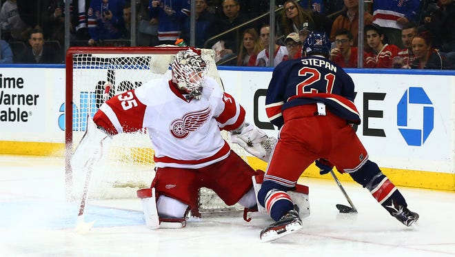 Red Wings goaltender Jimmy Howard (35) defends his net against Rangers center Derek Stepan (21) during the second period of the Wings' 1-0 overtime loss Sunday in New York.
