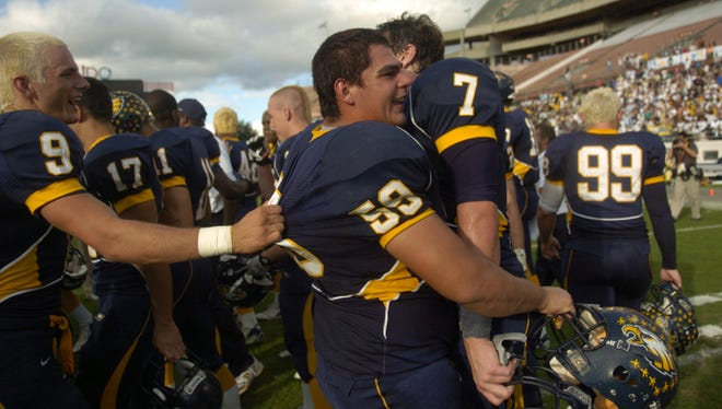 Naples High School football players Mike Zablo, Miguel De La Cruz, and Cody Frank celebrate their 17-10 win over St. Augustine in the 2007 FHSAA 3A Football Finals at the Citrus Bowl in Orlando.