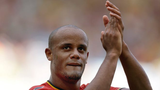 Belgium's Vincent Kompany applauds following Belgium's 1-0 victory over Russia during the group H World Cup soccer match between Belgium and Russia at the Maracana Stadium in Rio de Janeiro, Brazil, Sunday, June 22, 2014. (AP Photo/Natacha Pisarenko)
